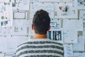 Cet entrepreneur de startup se pose des questions en comptabilité devant un tableau de liège.